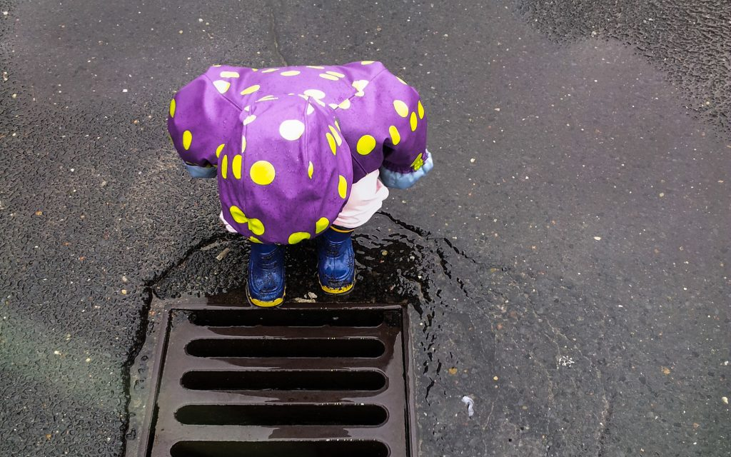 Photo of a child looking into a drain